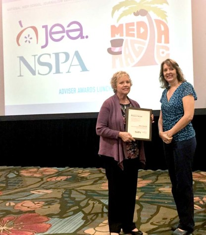 Mary Patrick, left, of Maize South Middle School accepts the Pioneer Award from NSPA board member Jeanne Acton at the Nov. 14 adviser awards lunch at the Orlando NSPA/JEA national convention.