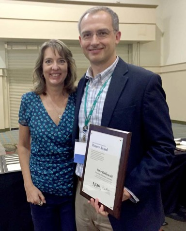 Peter Bobkowskie, right, of the University of Kansas accepts the Pioneer Award from NSPA board member Jeanne Acton at the Nov. 14 adviser awards lunch at the Orlando NSPA/JEA national convention.