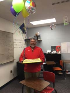 Dan Loving of Maize High School accepts balloons and a cake April 6 in recognition of winning the Sunflower Award.